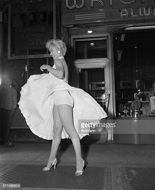Film star Marilyn Monroe poses over a Manhattan subway grate as the wind blows her white dress up Photographers capture the moment on camera which...