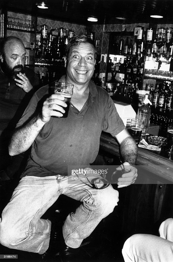 Film star Oliver Reed (1928 - 1999) pulls a face for the photographer while enjoying a pint of beer in a well stocked bar.