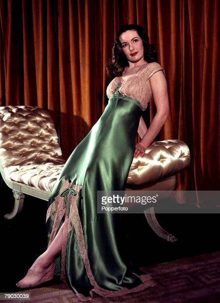 Film star Patricia Roc models a green satin nightdress trimmed with ecru lace designed by Honore 1947