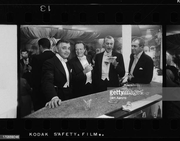 Film stars Clark Gable , Van Heflin , Gary Cooper and James Stewart enjoy a joke at a New Year's party held at Romanoff's in Beverly Hills.