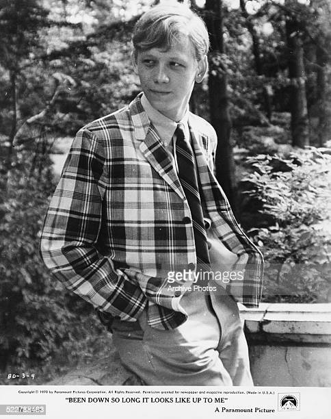 Film still of actor Bruce Davison wearing a checked jacket and tie standing on a porch in a scene from the movie 'Been Down So Long it Looks Up to...