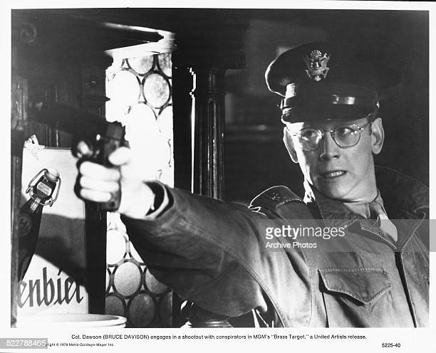 Film still of actor Bruce Davison wearing a makeshift military uniform and pointing a gun in a scene from the movie 'Brass Target' 1978