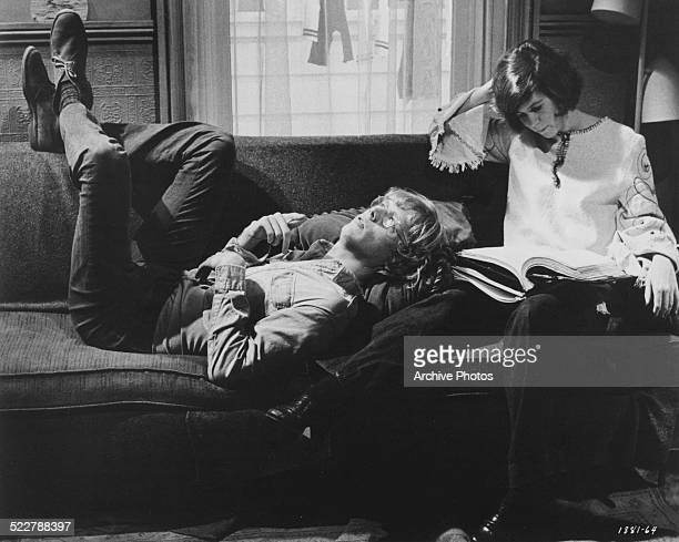 Film still of actors Bruce Davison and Kim Darby relaxing together on a couch in a scene from the movie 'The Strawberry Statement' 1970