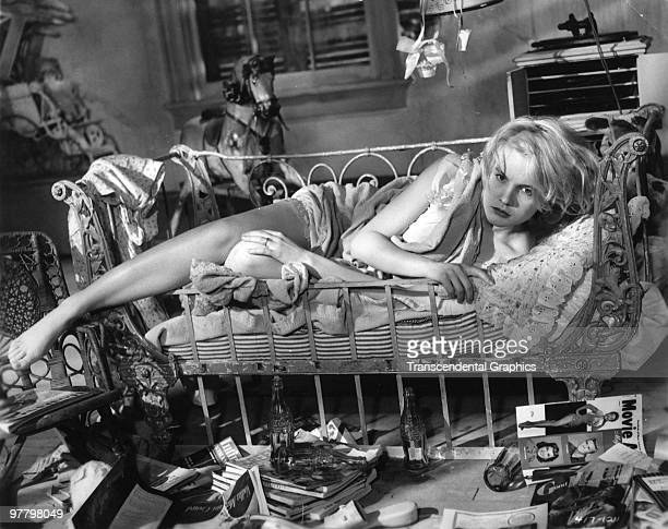 Film still of American actress Carroll Baker as she wakes from a nap in a crib surrounded by movie magazines and soda bottles in a scene from 'Baby...