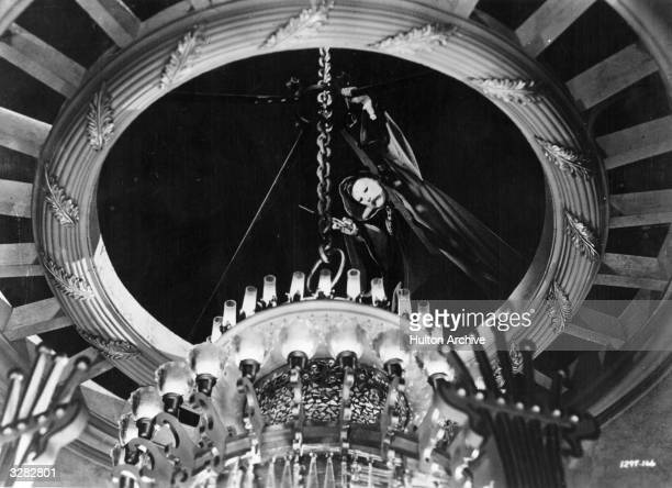 Film still shows British actor Claude Rains poised and about to cut the chain that holds the enormous chandelier in place in a scene from the film...