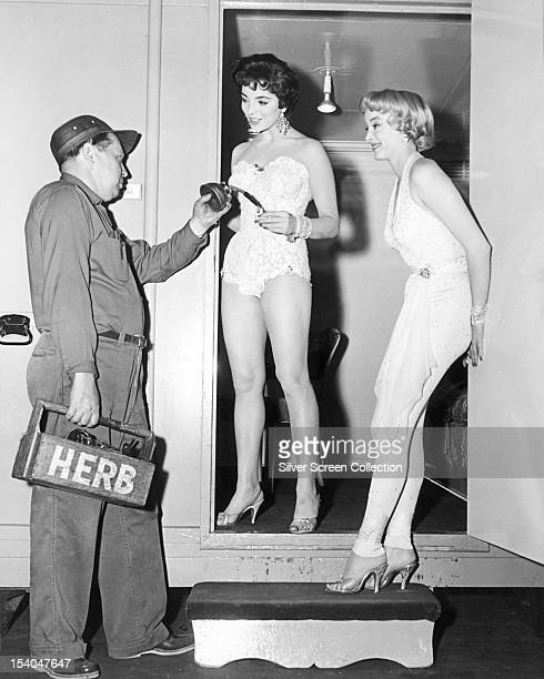 Film studio maintenance man fills a cigarette lighter for English actress Joan Collins outside her dressing room, as American actress Carolyn Jones...