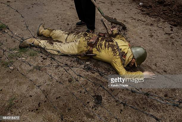 A film worker puts mud on a Chinese actor playing a dead Japanese soldier between scenes during the filming of the series 'The Last Noble' set during...