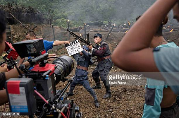 A film worker signals the take as Chinese actors playing Nationalist soldiers prepare for a scene during filming of a battle segment in the series...