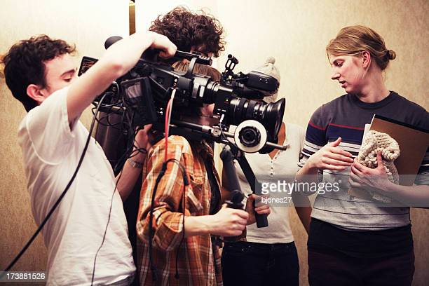 filming crew of three people shooting two girls talking - film crew stock pictures, royalty-free photos & images