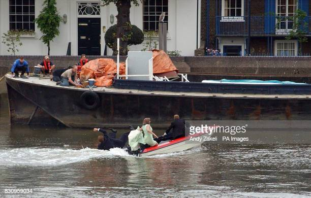 Filming of the movie 'Charlie' along the Thames River near Hammersmith Bridge starring Luke Goss Goss' stunt double driving the boat as it prepares...