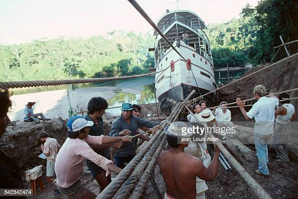 Filming on the set of Fitzcarraldo directed by Werner Herzog on location in Peru Crew members hauling the paddle steamer | Location Peru
