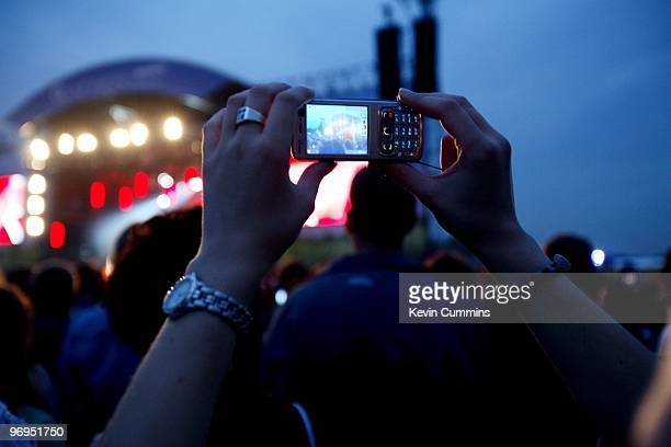 Filming with a mobile phone as the White Stripes perform on stage at the 02 Wireless Music Festival in Hyde Park London on June 14 2007