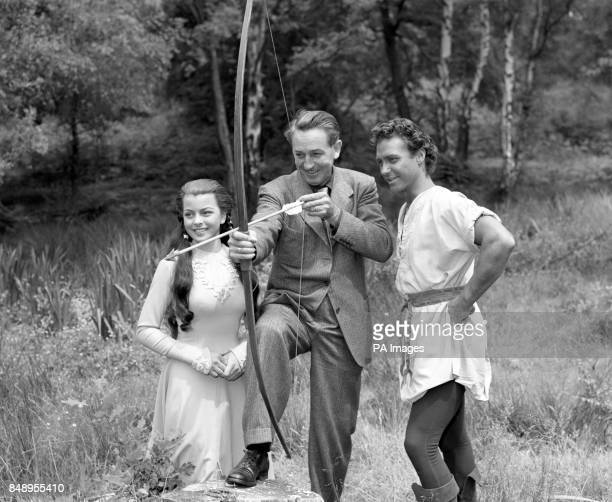 Filmland's Walt Disney, centre, shows a deft touch with a bow and arrow to Robin Hood actor Richard Todd and Maid Marian actress Joan Rice during a...