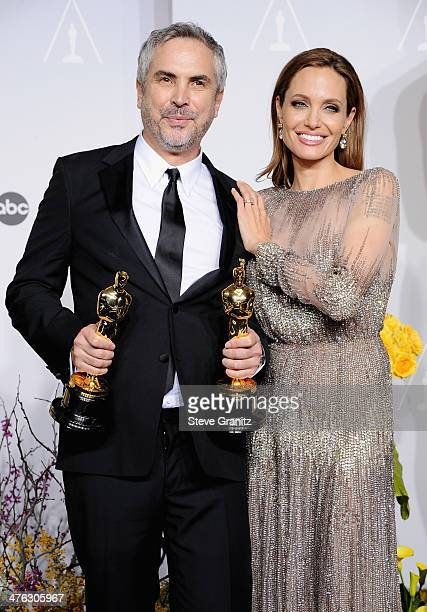 Filmmaker Alfonso Cuaron and actress Angelina Jolie pose in the press room during the Oscars at Loews Hollywood Hotel on March 2 2014 in Hollywood...