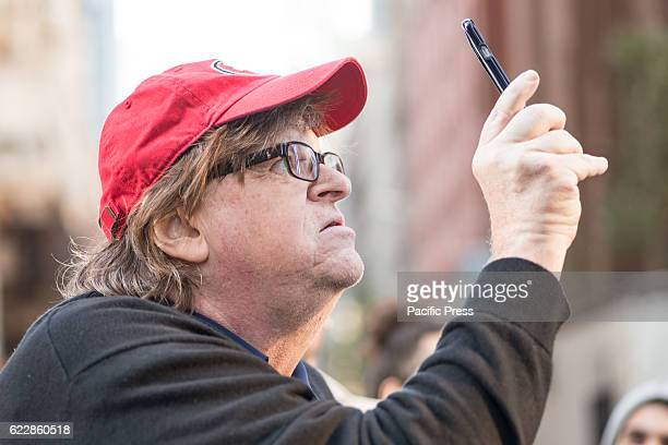 Filmmaker and political commentator Michael Moore is seen documenting demonstrators at their stopping point outside Trump Tower On the fourth day...