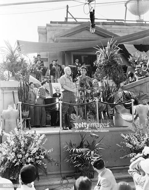 Filmmaker Cecil B DeMille and actor Henry Wilcoxon giving a speech to the cast and crew on the set of the film 'Samson and Delilah' for Paramount...