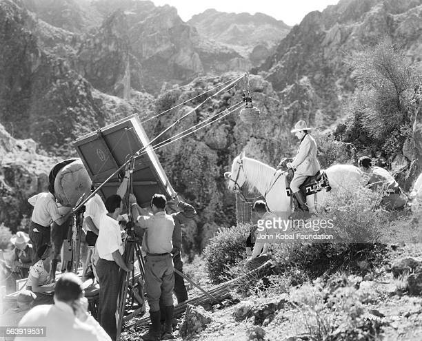 Filmmaker Cecil B DeMille and his crew filming a scene with an actor on horseback on the set of the film 'The Squaw Man' March 4th 1931