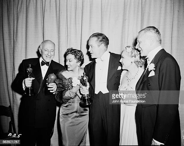 Filmmaker Cecil B DeMille holding his Best Picture Oscar for the film 'The Greatest Show on Earth' for Paramount Pictures with a group of people...