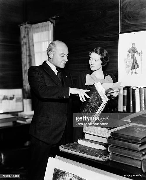 Filmmaker Cecil B DeMille looking through research and costume designs in preparation for his film 'The Crusades', for Paramount Pictures, 1935.