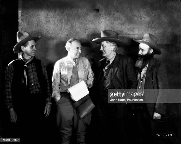 Filmmaker Cecil B DeMille talking to three actors on the set of the film 'The Squaw Man' for MGM Studios March 17th 1931