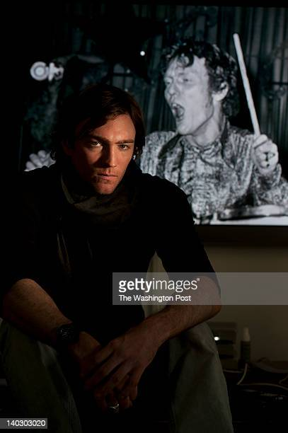 Filmmaker Jay Bulger poses for a portrait with an image of legendary rock drummer Ginger Baker shown behind him on Saturday February 04 2012 at the...