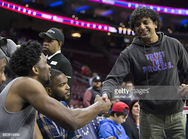 Filmmaker M Night Shyamalan shakes hands with Joel Embiid of the Philadelphia 76ers prior to the game against the LA Clippers at the Wells Fargo...