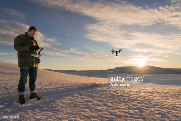 Filmmaker operating the control panel of the DJI Inspire 1 Drone on Hagafellsjokull Glacier in Iceland. The sun is about to set on the Mt Hagafell, Langjokull Ice Cap, Central Highlands of Iceland.  Date photographed: November 5, 2016