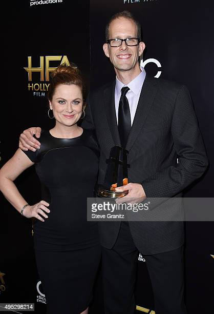 Filmmaker Pete Docter winner of the Hollywood Animation Award for Inside Out poses with actress Amy Poehler in the press room during the 19th Annual...