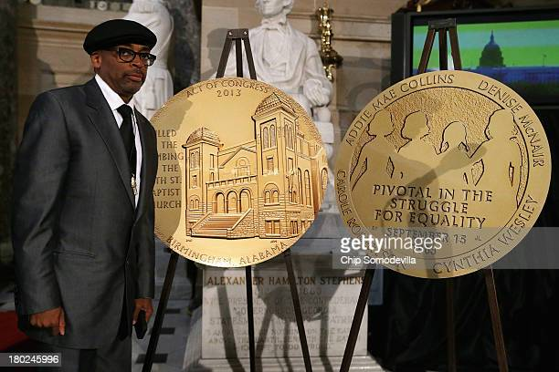 Filmmaker Spike Lee poses for a photograph next to a large reproduction of the Congressional Gold Medal that was posthumously awarded to the four...