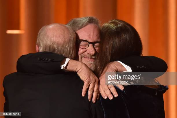 TOPSHOT US filmmaker Steven Spielberg embraces US producer Kathleen Kennedy and US producer Frank Marshall as they accept the Irving G Thalberg...
