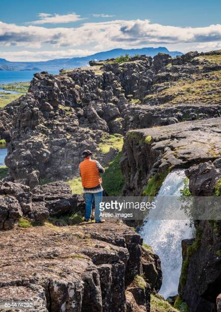 filmmaker working at thingvellir national park, iceland - thingvellir stock photos and pictures