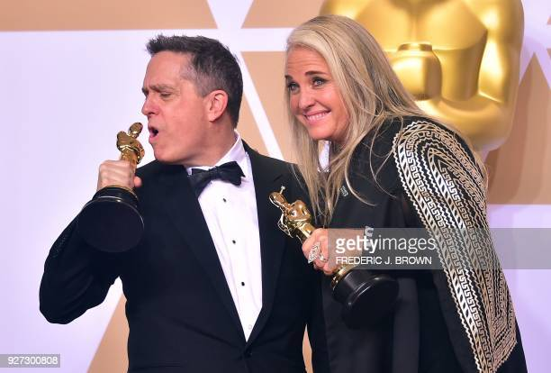 Filmmakers Lee Unkrich and Darla K Anderson pose in the press room with the Oscar for Best Animated Feature Film for Coco during the 90th Annual...