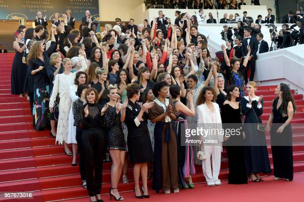 Filmmakers raise their arms as clap after Jury head Cate Blanchett with other filmmakers read a statement on the steps of the red carpet in protest...