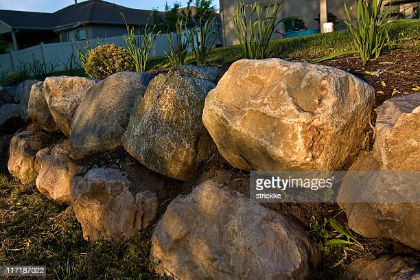 filtered golden sunlight iluminates rock retaining wall - retaining wall stock pictures, royalty-free photos & images