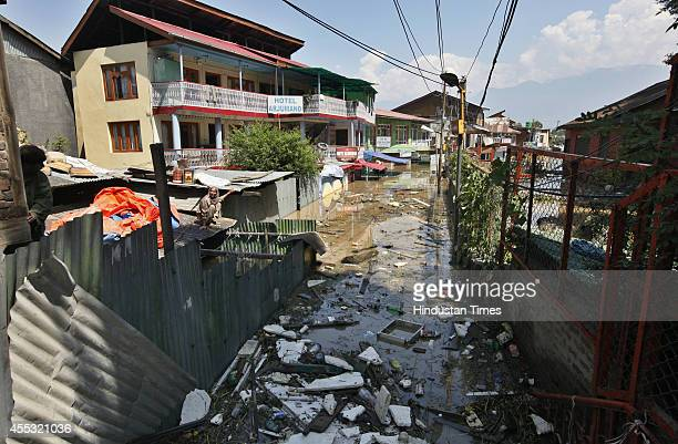 Filth brought by flood waters gathers at an entry to a residential area in Dal Gate area on September 11 2014 in Srinagar India Total of 130000...