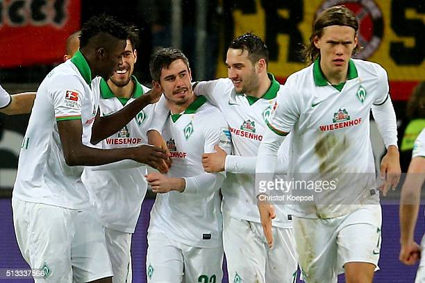 Fin Bartels of Bremen celebrates the first goal with Papy Djilobodji and Levin Oeztunali during the Bundesliga match between Bayer Leverkusen and...