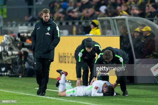 Fin Bartels of Bremen receives medical help and Head coach Florian Kohfeldt of Bremen looks on during the Bundesliga match between Borussia Dortmund...
