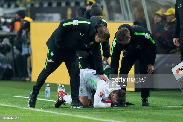 Fin Bartels of Bremen receives medical help and Head coach Florian Kohfeldt of Bremen helps during the Bundesliga match between Borussia Dortmund and...