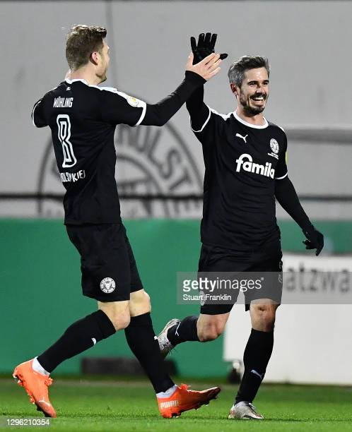 Fin Bartels of Holstein Kiel celebrates with teammate Alexander Muehling after scoring their team's first goal during the DFB Cup second round match...