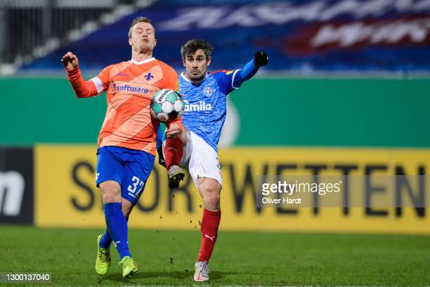 Fin Bartels of Holstein Kiel competes for the ball with Patrick Herrmann of SV Darmstadt 98 during the DFB Cup Round of Sixteen match between...