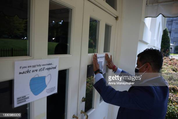 Fin Gomez, a journalist with CBS News and White House Correspondents Association board member, replaces signs for mask-wearing guidance around the...
