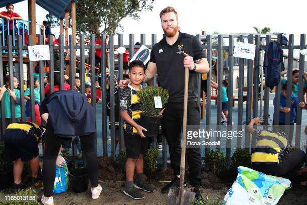 Fin Hoeata of Taranaki helps students of Koru School in Mangere plant shrubs during the Mitre 10 Cup Launch on July 30, 2019 in Auckland, New Zealand.