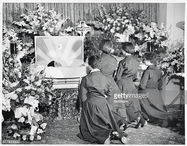Final Farewell to Emilie Callander Ontario The four surviving Dionne quintuplets are shown kneeling in prayer beside the casket of their quintsister...