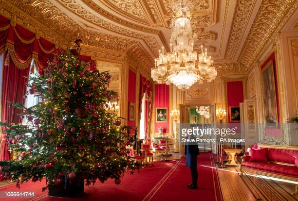 Final preparations are made to a 15ft Christmas tree in the Crimson Drawing Room at Windsor Castle Berkshire which is being decorated for Christmas