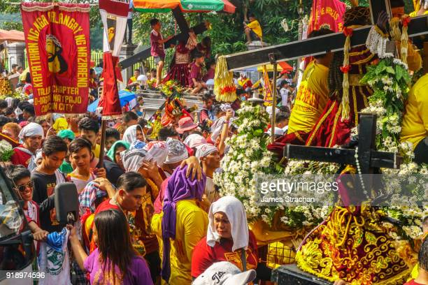 final procession of the annual feast of the black nazarene across manila starts at dawn and lasts 22 hours. ebony statue and cross of jesus (brought to philippines in 1606) carried through the streets, manila, philippines - black nazarene stock pictures, royalty-free photos & images
