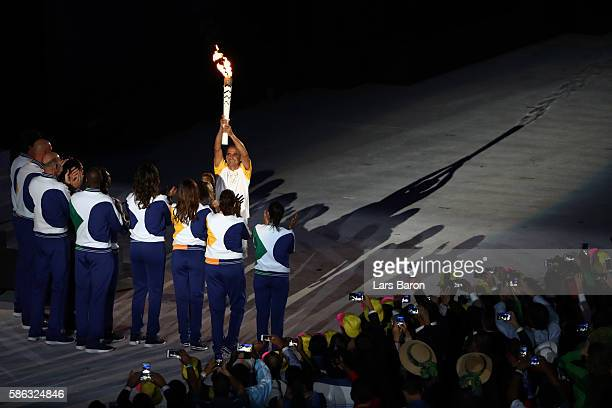 Final torch bearer Vanderlei Cordeiro de Lima lifts the torch before lighting the Olympic Cauldron during the Opening Ceremony of the Rio 2016...
