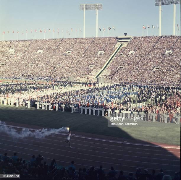 Final torch bearer Yoshinori Sakai runs during Tokyo Olympic Opening Ceremony at the National Stadium on October 10, 1964 in Tokyo, Japan.