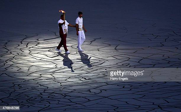 Final torchbearer Ilham Zakiyev is accompanied by Said Guliyev as he carries the flame into the stadium during the Opening Ceremony for the Baku 2015...