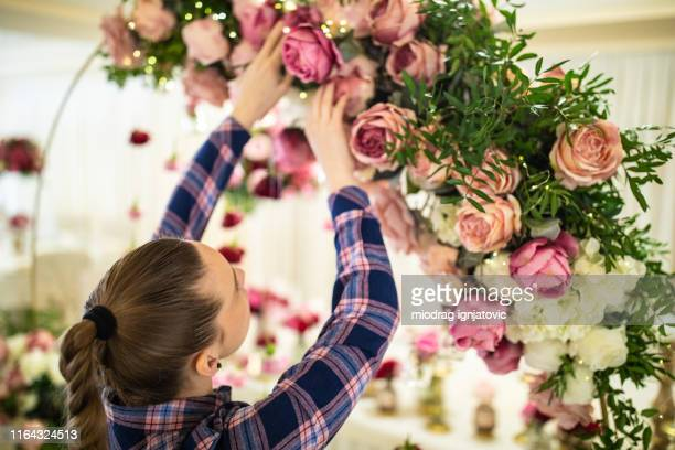 final touches to make beautiful flower decoration - wedding decoration stock pictures, royalty-free photos & images