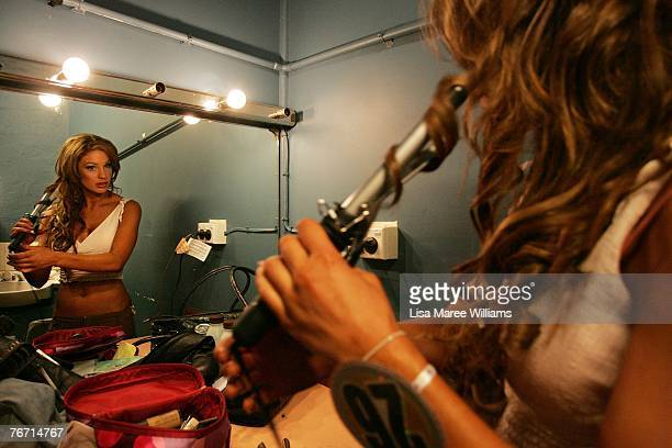 Finalist Sally Arnott curls her hair backstage during the Miss Earth Australia contest at the Enmore Theatre September 13 2007 in Sydney Australia...